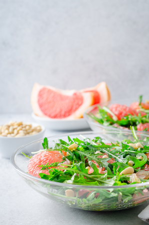 Grapefruit and arugula salad with pine nuts in glass bowls on a light gray stone concrete table. Vertical image, copy space Stock Photo