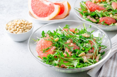 Grapefruit and arugula salad with pine nuts in glass bowls on a light gray stone concrete table. Horizontal image, high angle view