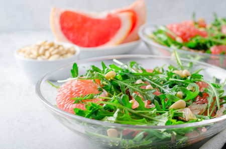 Grapefruit and arugula salad with pine nuts in glass bowls on a light gray stone concrete table. Horizontal image, close-up