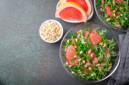 Grapefruit and arugula salad with pine nuts in glass bowls on a dark stone concrete table. Horizontal image, top view, copy space