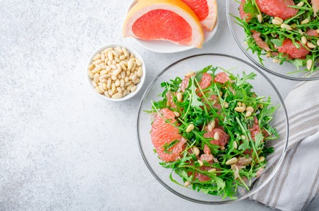 Grapefruit and arugula salad with pine nuts in glass bowls on a light gray stone concrete table. Horizontal image, top view, copy space