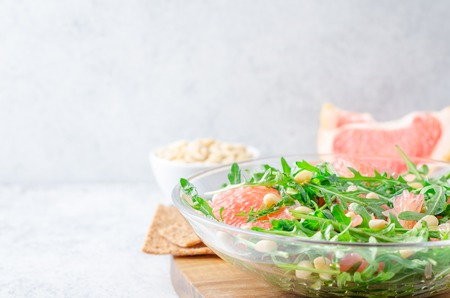 Grapefruit and arugula salad with pine nuts in glass bowls on a light gray stone concrete table. Horizontal image, front view, copy space 写真素材