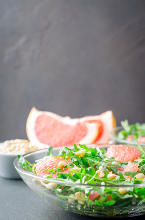 Grapefruit and arugula salad with pine nuts in glass bowls on a dark stone concrete table. Vertical image, copy space, front view