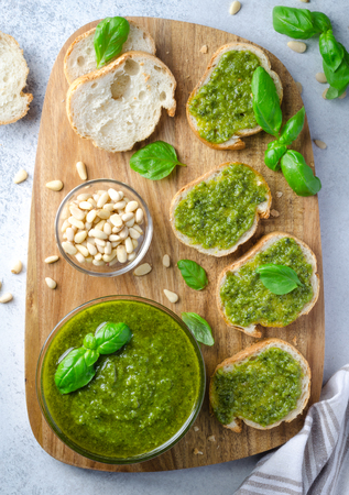 Pesto sauce with sliced bread on a wooden board on a light stone table. Vertical image, top view