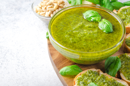 Pesto sauce with sliced bread and basil on a wooden board on a light stone table. Horizontal image, high angle view, copy space