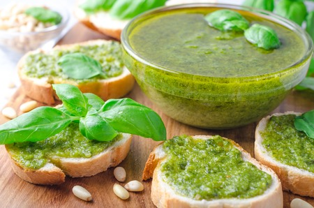 Pesto sauce with sliced bread and basil on a wooden board on a light stone table. Horizontal image, front view, copy space