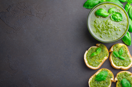 Pesto sauce with sliced bread and basil on a dark black stone table. Horizontal image, top view, copy space