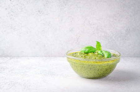 Pesto sauce with sliced bread and basil on a light stone table. Horizontal image, front view, copy space 写真素材