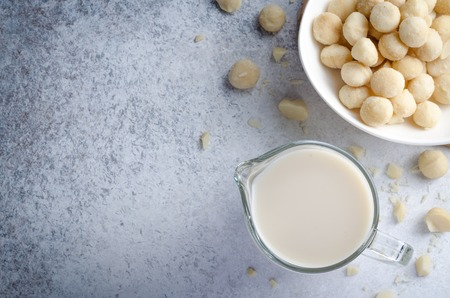 Macadamia milk in a glass pitcher and a bowl of macadamia nuts on a light blue stone background. Horizontal image, top view, copy space 写真素材