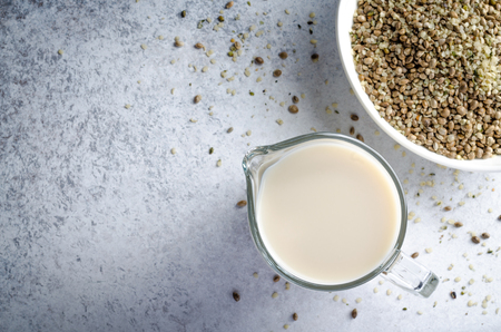Hemp seed milk in a glass pitcher and a bowl of hemp on a light blue stone background. Horizontal image, top view, copy space