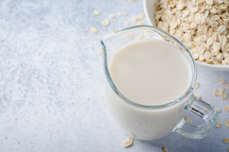 Oat milk in a glass pitcher and a bowl of oats on a light blue stone background. Horizontal image, high angle view, copy space
