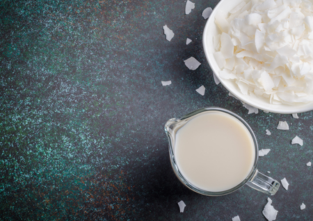 Coconut milk in a glass pitcher with coconut chips on a dark stone background. Horizontal image, top view, copy space 写真素材