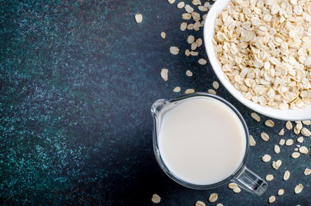 Oat milk in a glass pitcher on a dark stone background. Horizontal image, top view, copy space