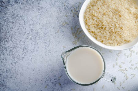 Rice milk in a glass pitcher and a bowl of rice on a light blue stone background. Horizontal image, top view, copy space