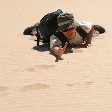 lie down: young man in desert, sand