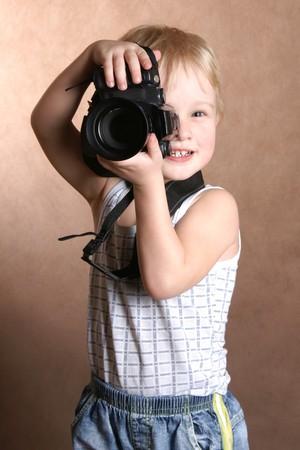 child in studio with professional camera photo
