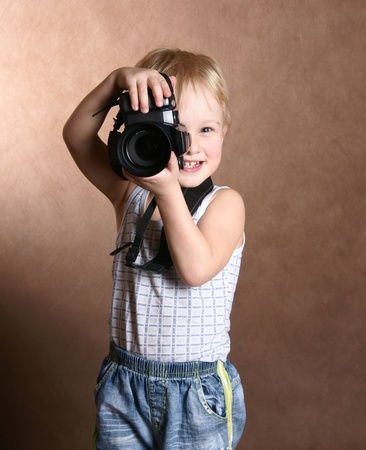 child in studio with professional camera photo