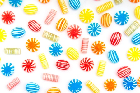 many different color candies on white photo