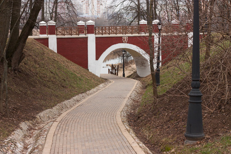 Arch brick footbridge with wooden railing in the city park and footpath beneath photo