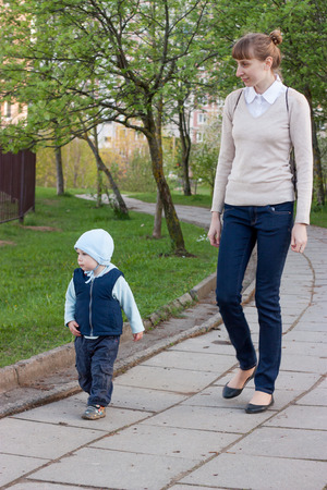 singly: Mother and son walk in the city park