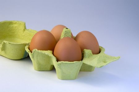 four eggs in yellow basket, isolated photo