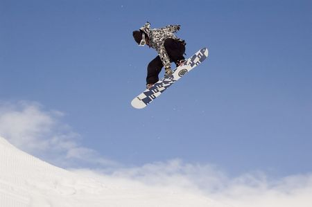 snowboarder jumping high in the air while performing a grab Stock Photo