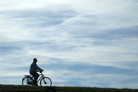 vacationer: silhouet of a man riding a bike, isolated on blue sky