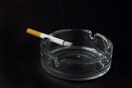 burning cigarette in ashtray isolated on black background photo