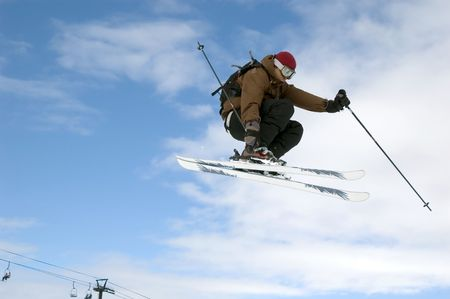 a skier jumping high through a blue sky
