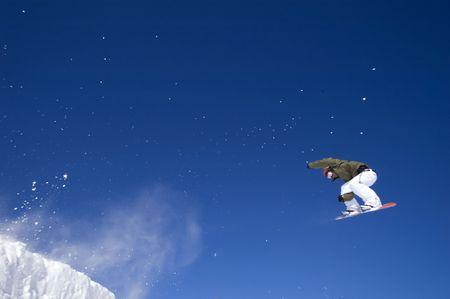 a snowboarder jumping high through a blue sky