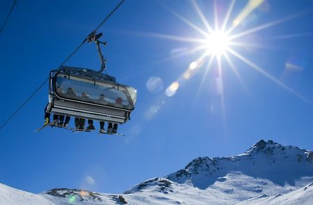 wintersport: skiers in a chairlift backlit by the sun and spreading sunflares
