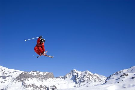 a skier jumping high through a blue sky, with mountain range in background