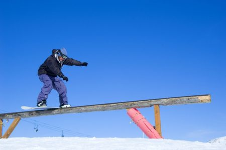 wintersport: a snowboarder boardsliding on a wooden rail