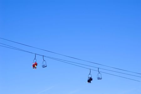 skiers and snowboarders in a chairlift against blue cloudless sky photo