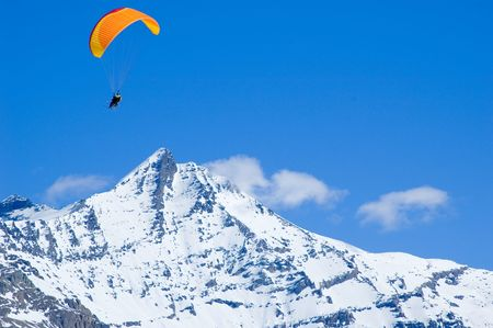 parapente: an orange glider circling above snowed mountains