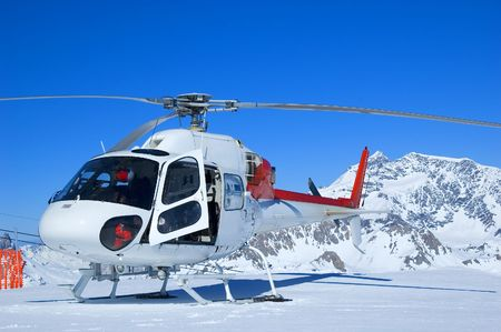 red and white rescue helicopter parked in the mountins