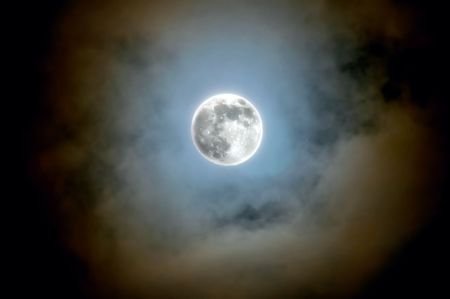 full moon shines through the clouds Stock Photo