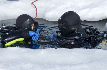 ascend: two divers rising on the surface between the ice Stock Photo