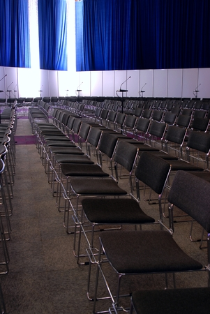 conference room with rows of chairs, blue curtains, white drapes, microphones photo