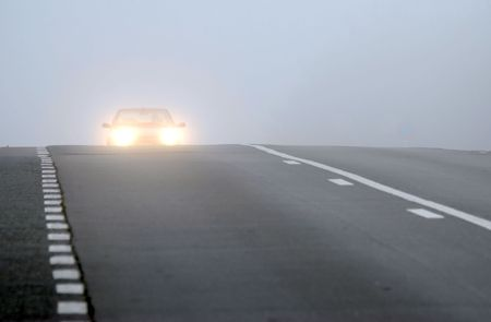 Car appearing through fog with headlights on