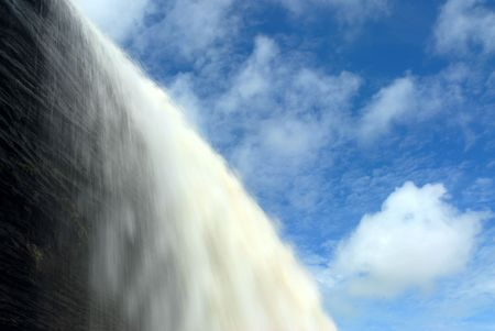 Water falls over a cliff surrounded by a blue sky with clouds.