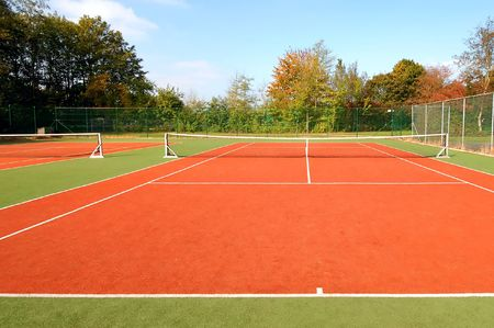 tennis court under blue sky, with autumn trees on the side.