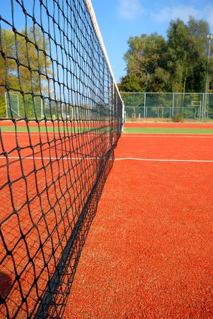 tennis court under blue sky, the net as leading line (wide angle) Stock Photo