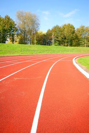 racetrack: racetrack, red tarmac, for runners. trees in the background