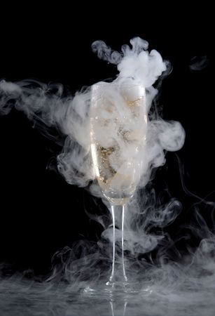 Glass of white wine isolated over black background, with lots of smoke
