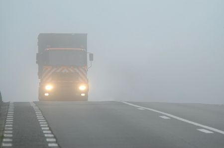 Truck appearing through fog with headlights on