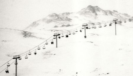 chairlift: Vintage image of people in chairlift with mountain in the background and copyspace Stock Photo