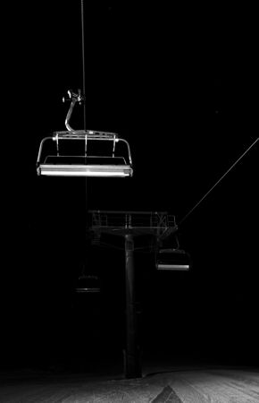 Chairlifts disappearing in the dark of the night photo