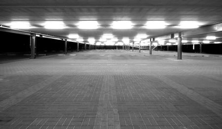 tl: an empty spacious parking lot by night in black and white