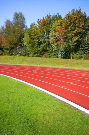 red race track with grass, trees and clear blue sky Stock Photo - 2608336